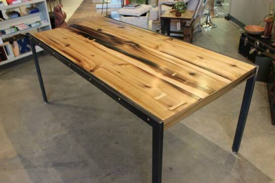 Dining room table made from poplar wood with butterfly splines supported by dark grey metal legs.