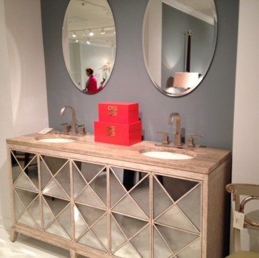 Convex mirrors incorporated into a unique double vanity with light wood tones.