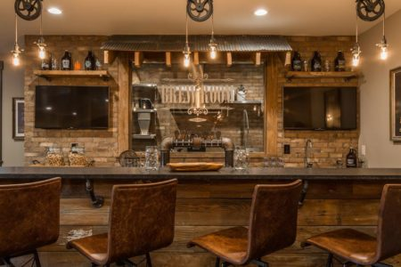 Rustic and industrial materials used to create this unique lower level bar in the G&G Custom Home designed by Hilari Goris.